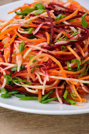 celery root: plate salad of shredded raw beets, and carrots  on celery root  close-up