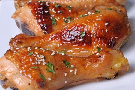 nosh: Fried chicken leg with sesame seeds in a plate closeup