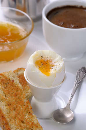 elevenses: Soft-boiled egg with cup of coffee, toast and jam for breakfast