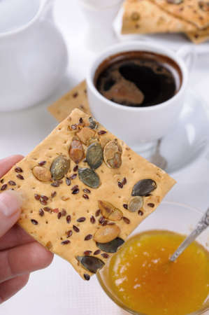elevenses: holding the hand of gluten free crackers with cereals for breakfast