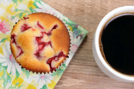 morsel: Muffin filled with strawberries on a table  cup of coffee Stock Photo