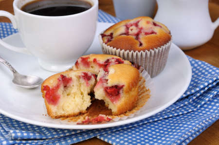 elevenses: Break muffin with strawberries on a table cup of coffee