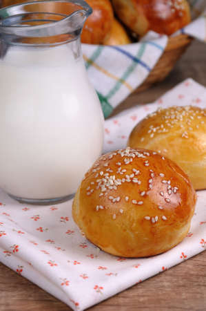 breadbasket: Buns with sesame seeds and a jug of milk on the table