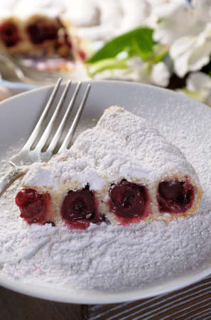 a piece of cherry pie sprinkled with powder sugar on a plate