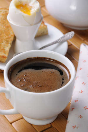 A cup of coffee with a soft-boiled egg and toast for breakfast