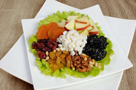 Vitamin salad with nuts, apples, dried fruit and cottage cheese in lettuce leaves Stock Photo