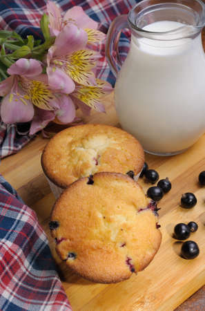 elevenses: Muffins with filling  the table with carafe of milk and berries Stock Photo