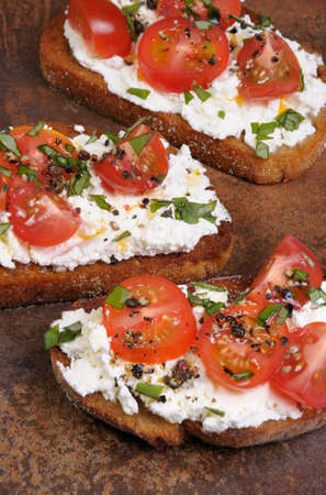 Bruschetta with ricotta and cherry tomatoes seasoned   spices, basil