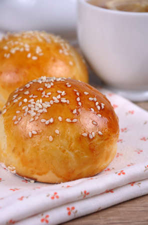 Buns with sesame seeds in a basket on table