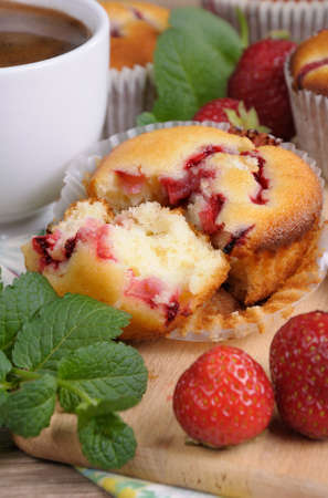 elevenses: Break muffin with strawberries on a table among the berries and mint