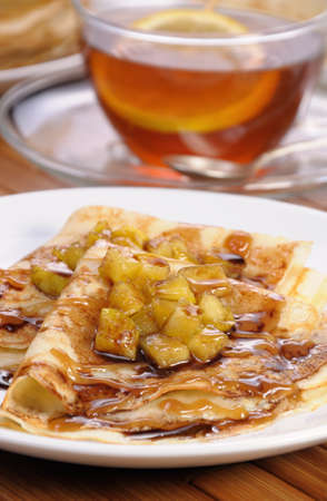 morsel: Breakfast pancakes on apples with caramel and chocolate and cup of tea