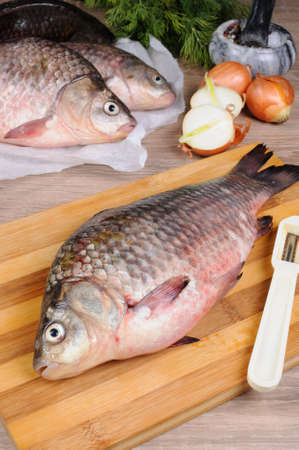 limnetic: Fresh crucian carp lying on a cutting board for cutting cooked Stock Photo