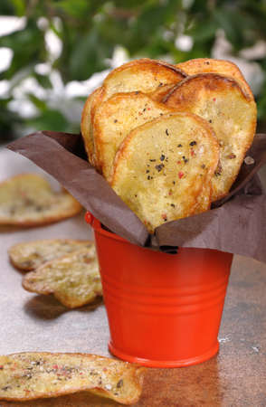 nosh: Homemade potato chips wrapped in paper and folded  bucket Stock Photo