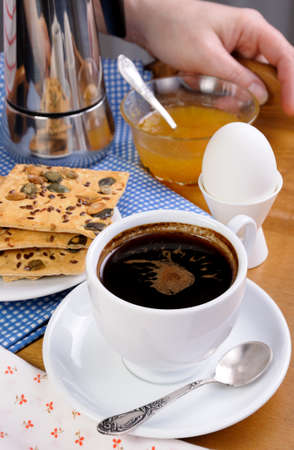 sesame cracker: A cup of coffee with a soft-boiled egg and toast for breakfast