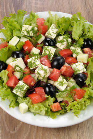 Salad of lettuce with diced olives, tomato, cucumber, feta at dill