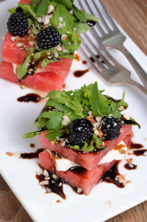 elevenses: appetizer  stacked slices of watermelon, feta, arugula, blackberry sauce and nuts Stock Photo