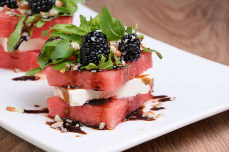 appetizer  stacked slices of watermelon, feta, arugula, blackberry sauce and nuts Stock Photo