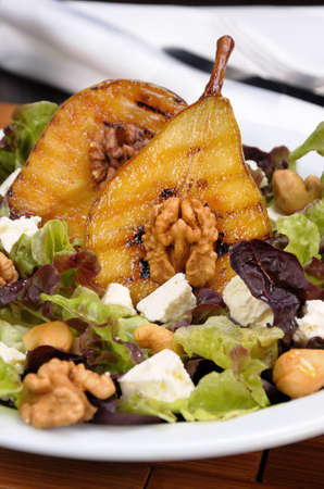 Salad of lettuce with   walnuts, cashews, slices  feta,  halves of caramelized pear