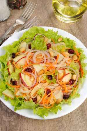 Dietary salad with apples, daikon, carrots, lettuce ,  cranberries and peanuts