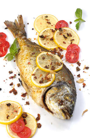 gilthead bream: roasted fish  Dorado with lemon slices and tomatoes flavored   spices Stock Photo