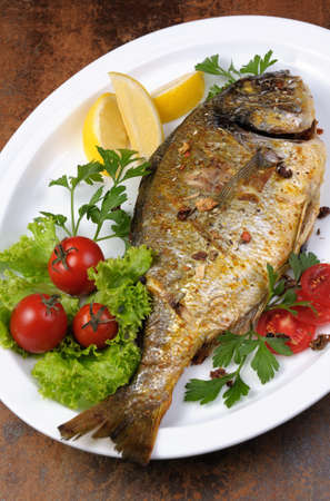 elevenses: roasted fish  Dorado  with vegetables  garnish and lemon slices  on a plate Stock Photo