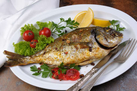 gilthead bream: roasted fish  Dorado  with vegetables  garnish and lemon slices  on a plate Stock Photo