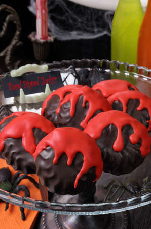 immersed: Zephyr in chocolate glaze with a bloody streaks   the table on Halloween Stock Photo