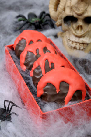 pastila: Zephyr in chocolate glaze with a bloody streaks   the table on Halloween Stock Photo