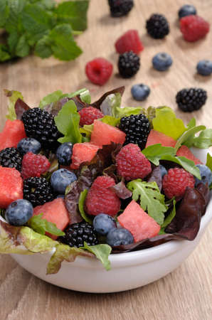 lunch hour: Fruit salad with blackberry, raspberry, blueberry, watermelon slices and mix of green leaves Stock Photo