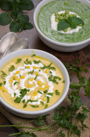 two bowl of puree soup mealies and pea with herbs Stock Photo