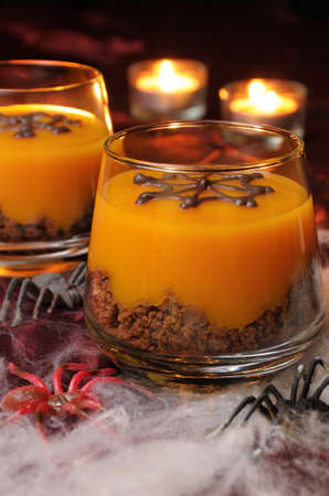 Dessert from biscuit and pumpkin cream in a glass of decorated chocolate  web for Halloween