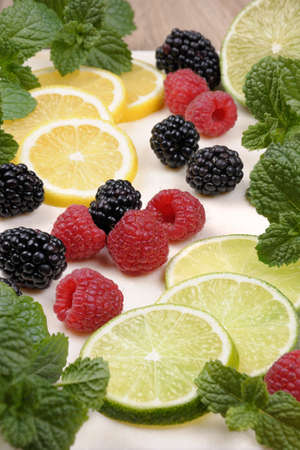 elevenses: scattered blackberries and raspberries with lime and lemon slices, mint twigs