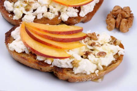 Sandwich of oat bread with ricotta and slices of peach, nuts, watering honey Stock Photo