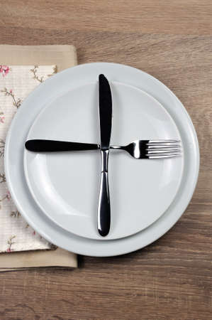 Dining etiquette - I still eat, ready for second plate. Fork and knife signals with location of cutlery set Foto de archivo