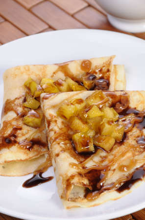 Pancakes sliced apples with caramel and chocolate for breakfast Stock Photo
