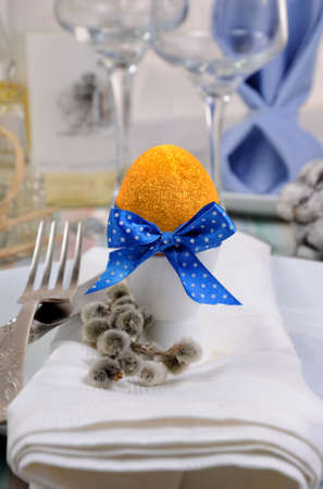 Decorations for Easter.   Golden egg  cups tied with a ribbon on a napkin.