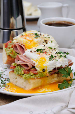 poached  eggs with avocado, tomatoes, slices of ham on a baguette for breakfast Standard-Bild