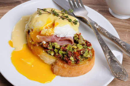 Toasted baguette slice with guacamole, ham and eggs Benedict under Dutch sauce Stock Photo