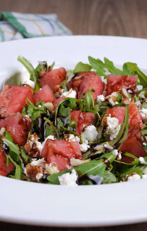 Arugula salad, ricotta cheese with watermelon slices,  balsamic soy sauce Stock Photo