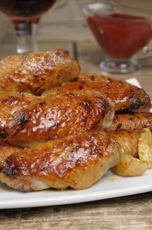 sharply: Fried sharply spicy chicken wings on a baking c sauce