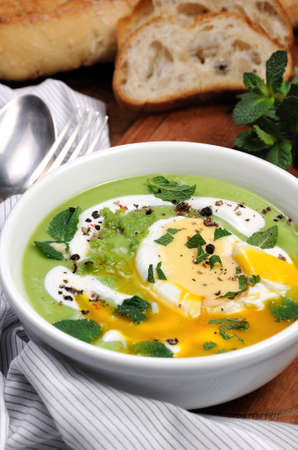 Pea puree soup with poached egg, sour cream, mint leaves seasoned with spices.