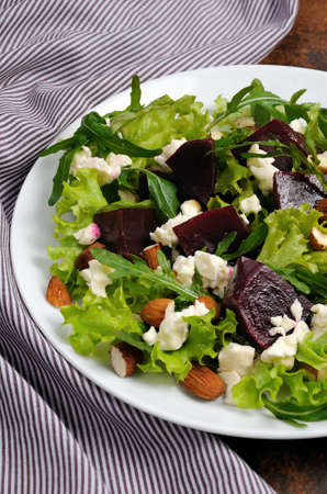 Salad vinaigrette with beets, lettuce, arugula, feta, and almonds,