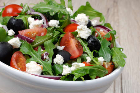 Variation of Greek salad with arugula, cherry slices, feta and olives