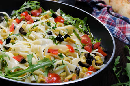 Pasta with crushed olives and cherry tomatoes, arugula. Horizontal shot. Stock Photo