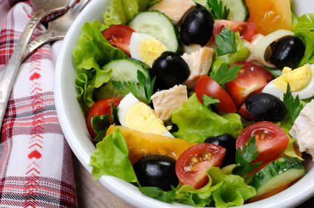 Vegetable salad with chicken and eggs, olives in lettuce leaves. Horizontal shot. Close-up.