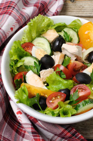 Vegetable salad with chicken and eggs, olives in lettuce leaves. Vertically  shot.