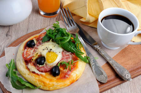 Mini pizza with sausage and egg and arugula, a cup of coffee for breakfast Stock Photo - 80089490
