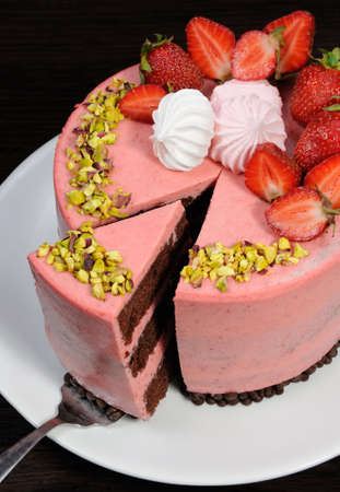 A cut piece of chocolate strawberry mousse cake decorated with berries, meringue and pistachios