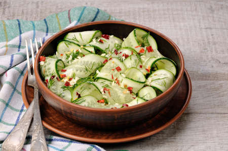 stripping: A bowl of salad from cucumber strips with spices, garlic and dill. Rustic style.