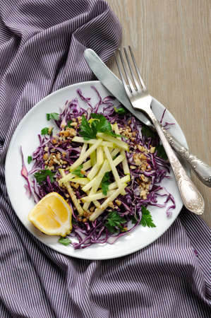 Salad red coleslaw with apple slices and crushed walnut